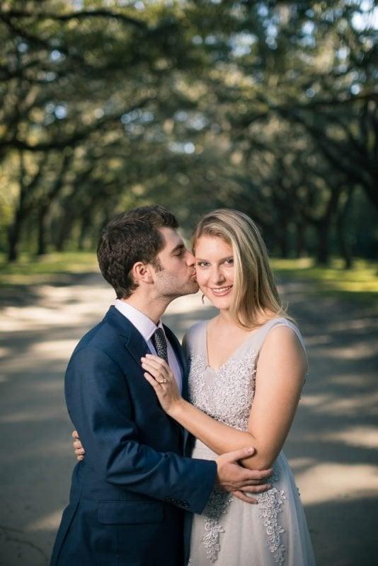 groom kisses bride on cheek under trees of wormsloe plantation Savannah