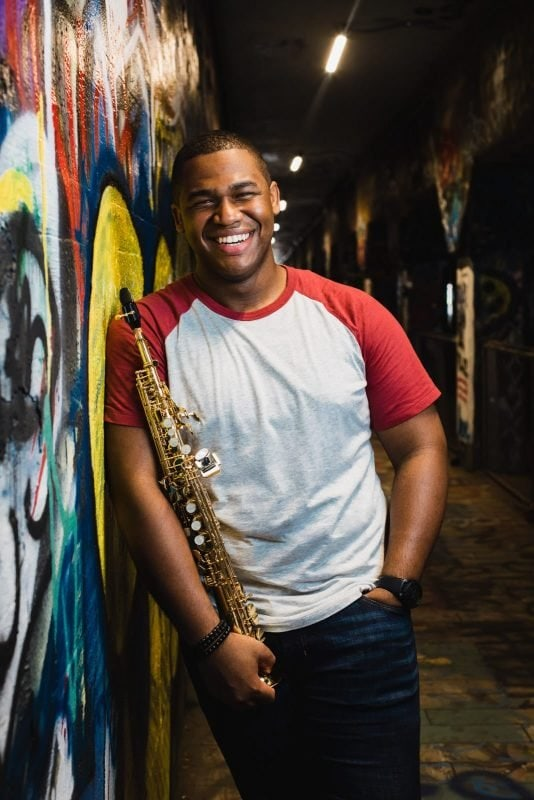musician leaning on graffiti wall with saxophone krog street tunnel