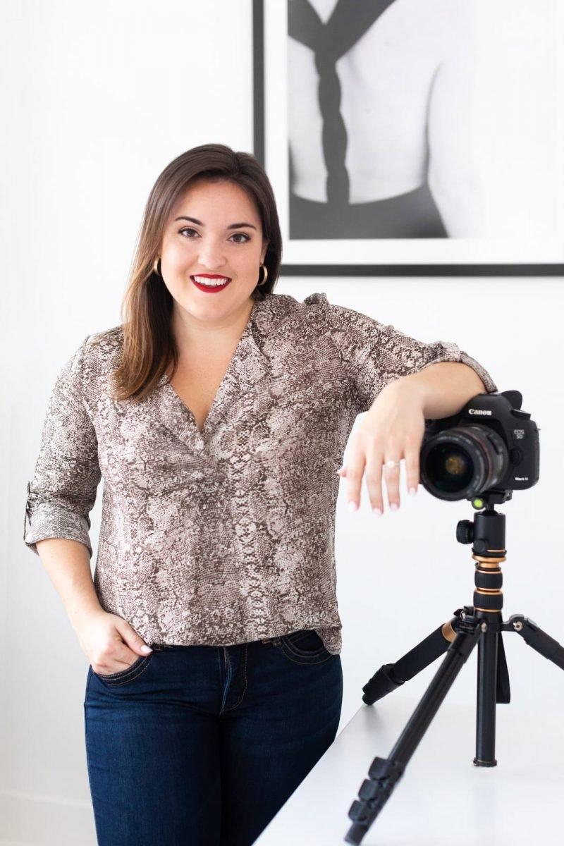 female freelancer leans on camera and desk at white wall studio woodstock atlanta