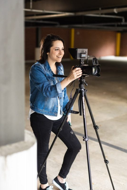 atlanta videographer smiles with camera on tripod