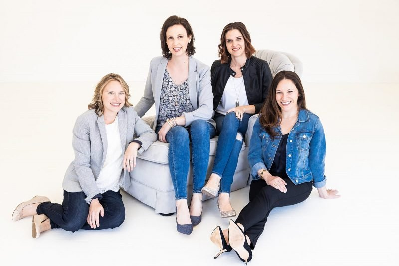 atlanta small business portrait female entrepreneurs sitting on couch wearing complimentary outfits white wall studio Woodstock