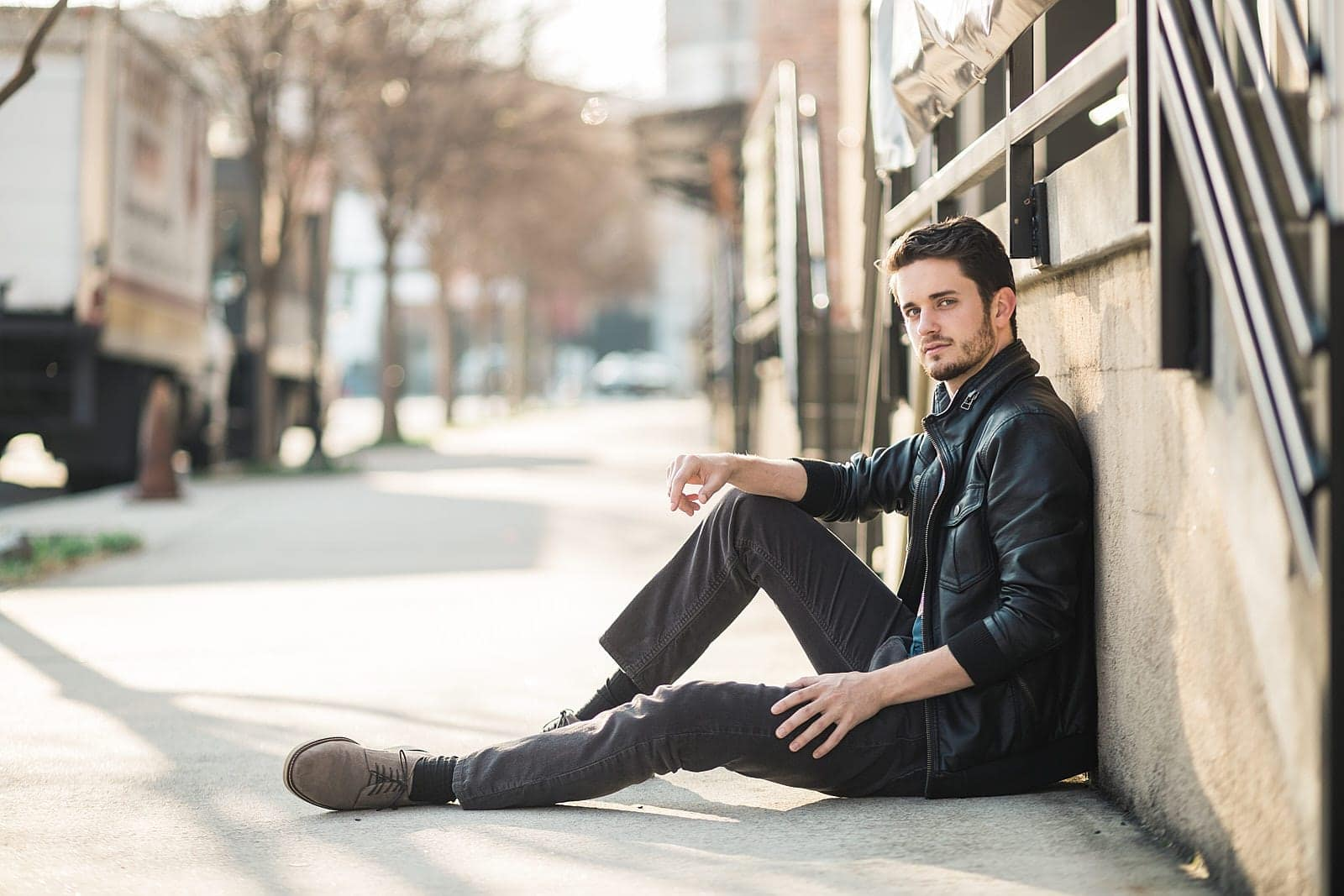 atlanta male actor in leather jacket sits on sidewalk of west midtown