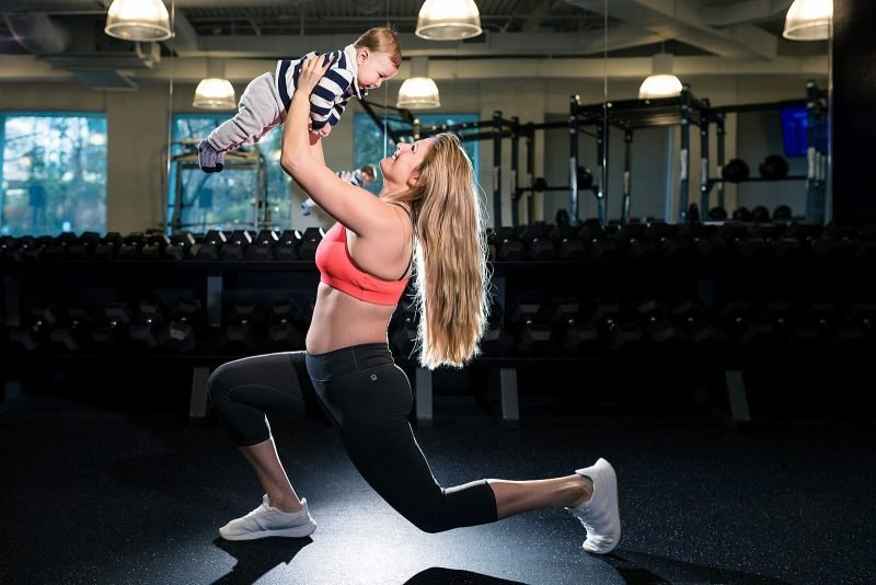 atlanta fitness mom raises son above head in gym wearing athletic gear
