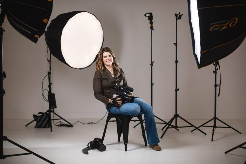 atlanta branding portrait of videographer surrounded by lights at white wall studio woodstock