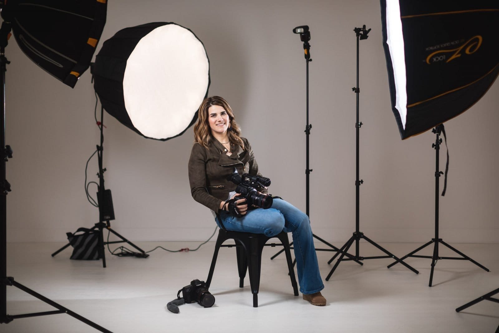 atlanta branding studio portrait of videographer surrounded by lights at white wall studio woodstock