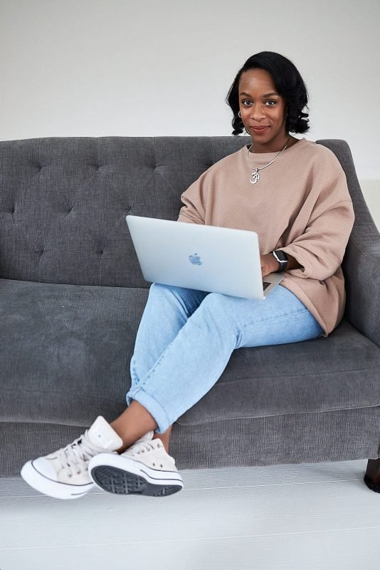female entrepreneur works on laptop sitting on white wall woodstock couch