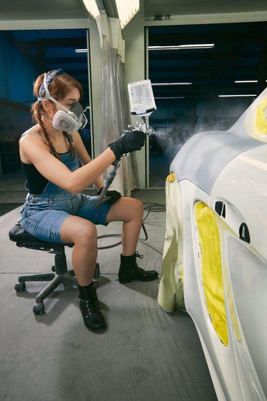 female worker paints car at atlanta repair shop