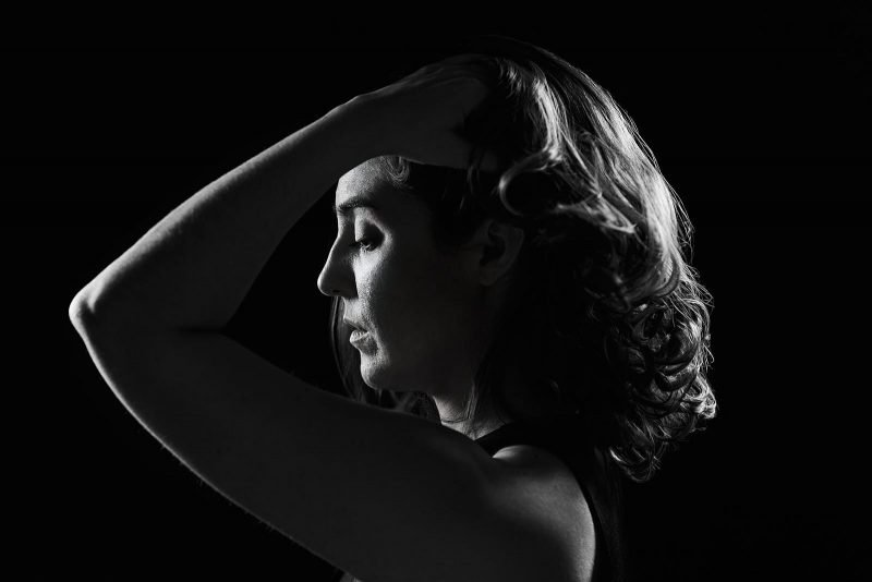 black and white rim lighting portrait of girl running fingers through hair atlanta studio