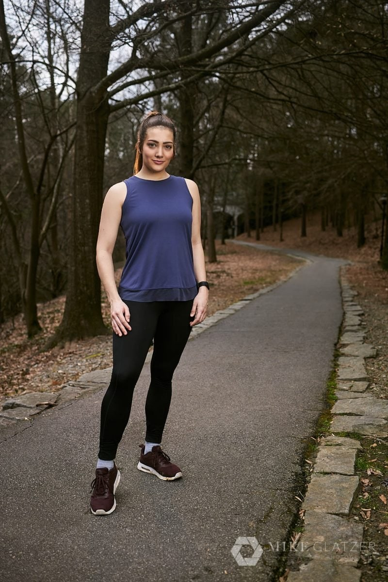 female trail runner stands on path of atlanta park