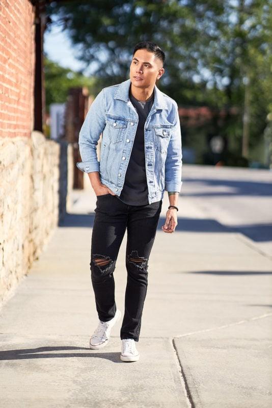flash portrait of man in jean jacket walking on urban sidewalk in direct sunlight
