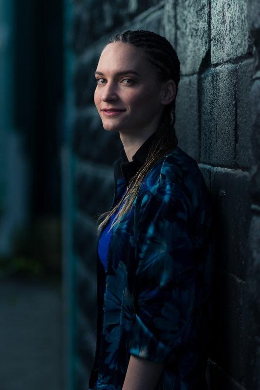 high speedy sync flash portrait of girl leaning against brick wall