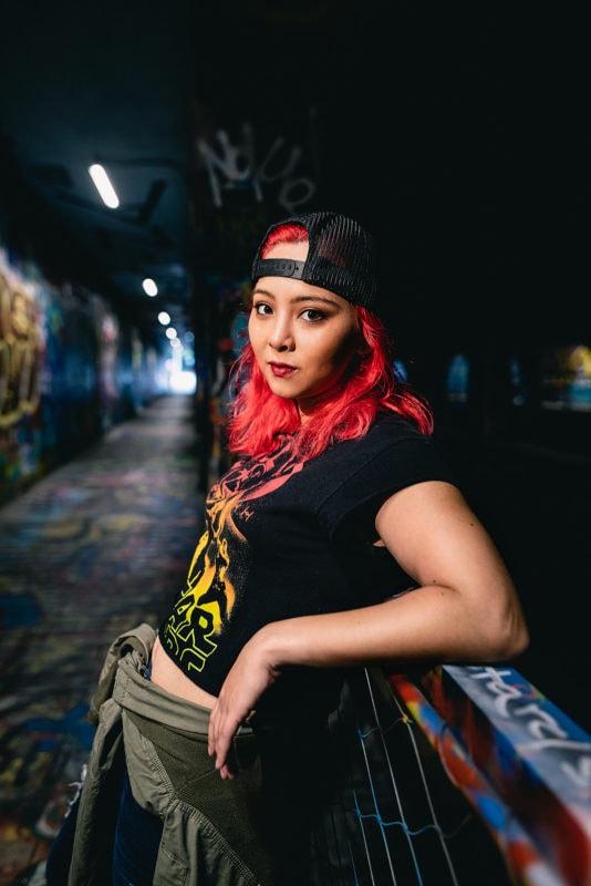 punk skater girl leaning on railing of graffiti tunnel portrait