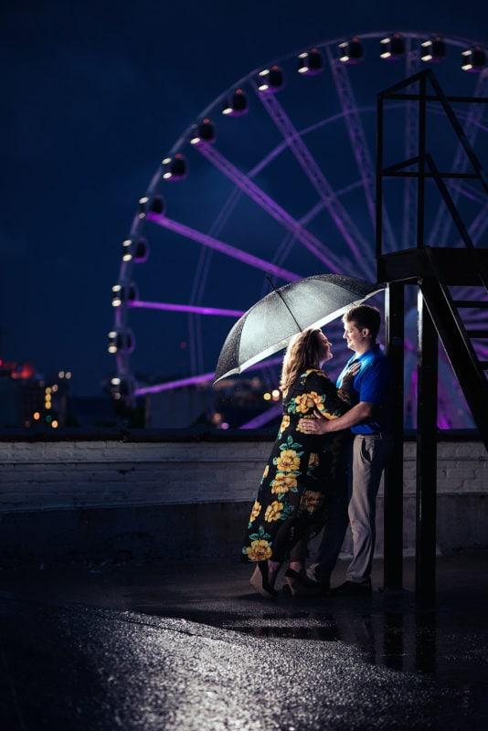 engaged couple under umbrella at night