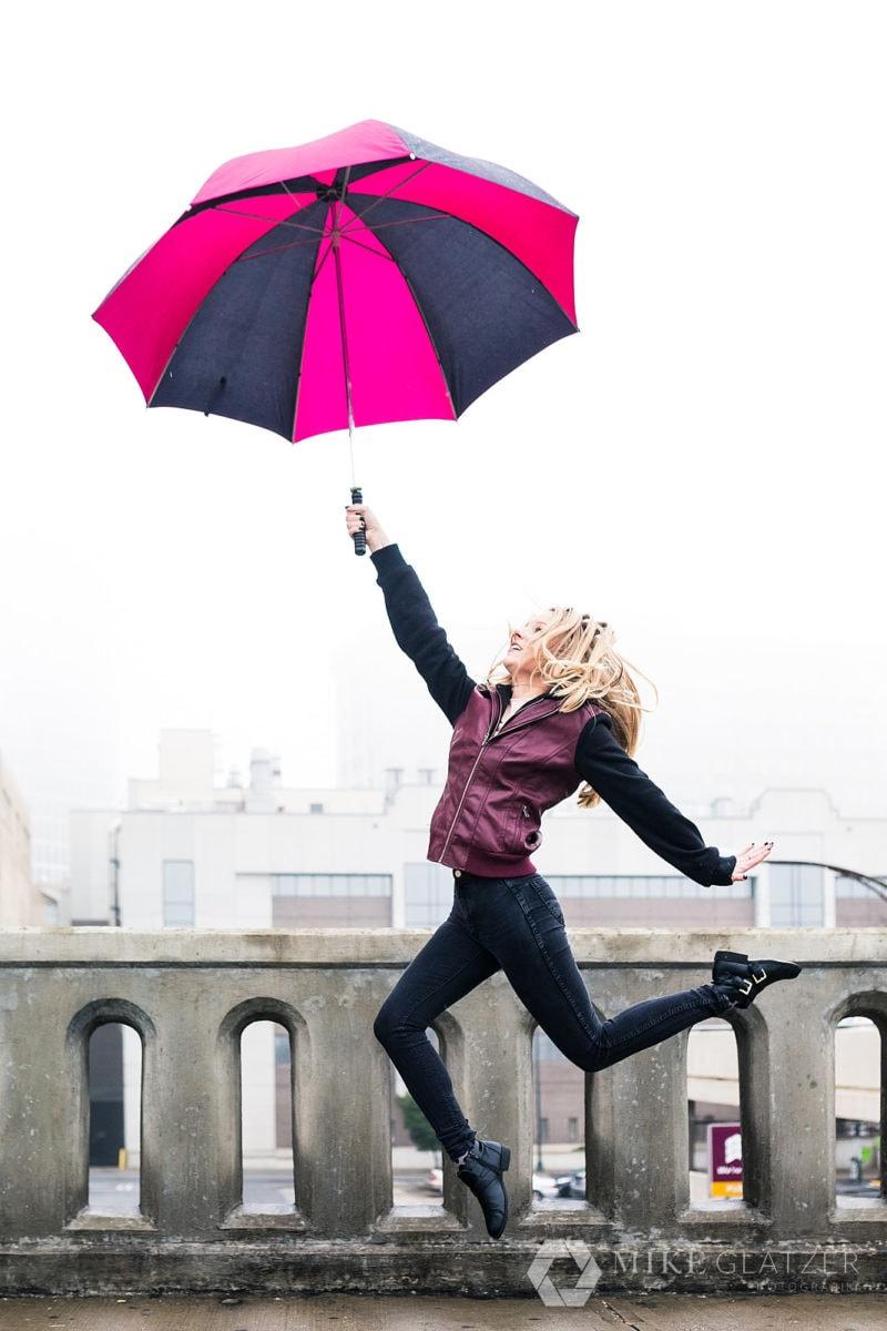 girl leaps with umbrella for rainy photoshoot in downtown atlanta