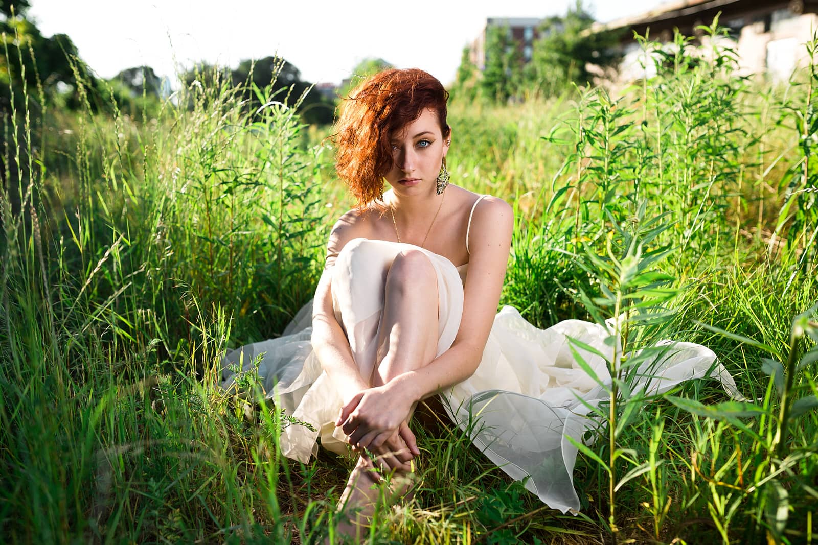 red head girl in white dress sits in greed field for atlanta portrait photography
