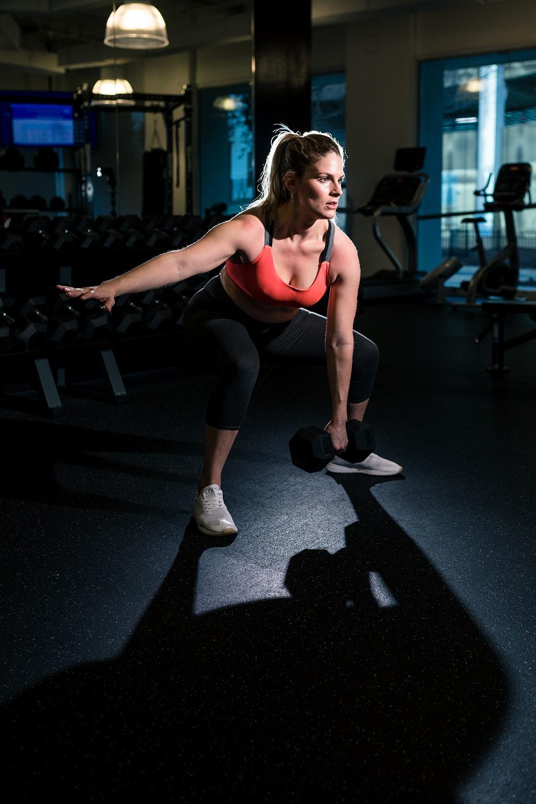dramatic portrait of mom lifting weights in Atlanta gym