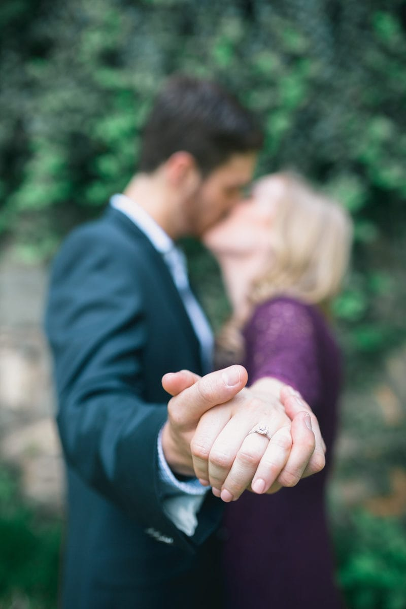 engaged couple kisses and shows off ring at Piedmont Park