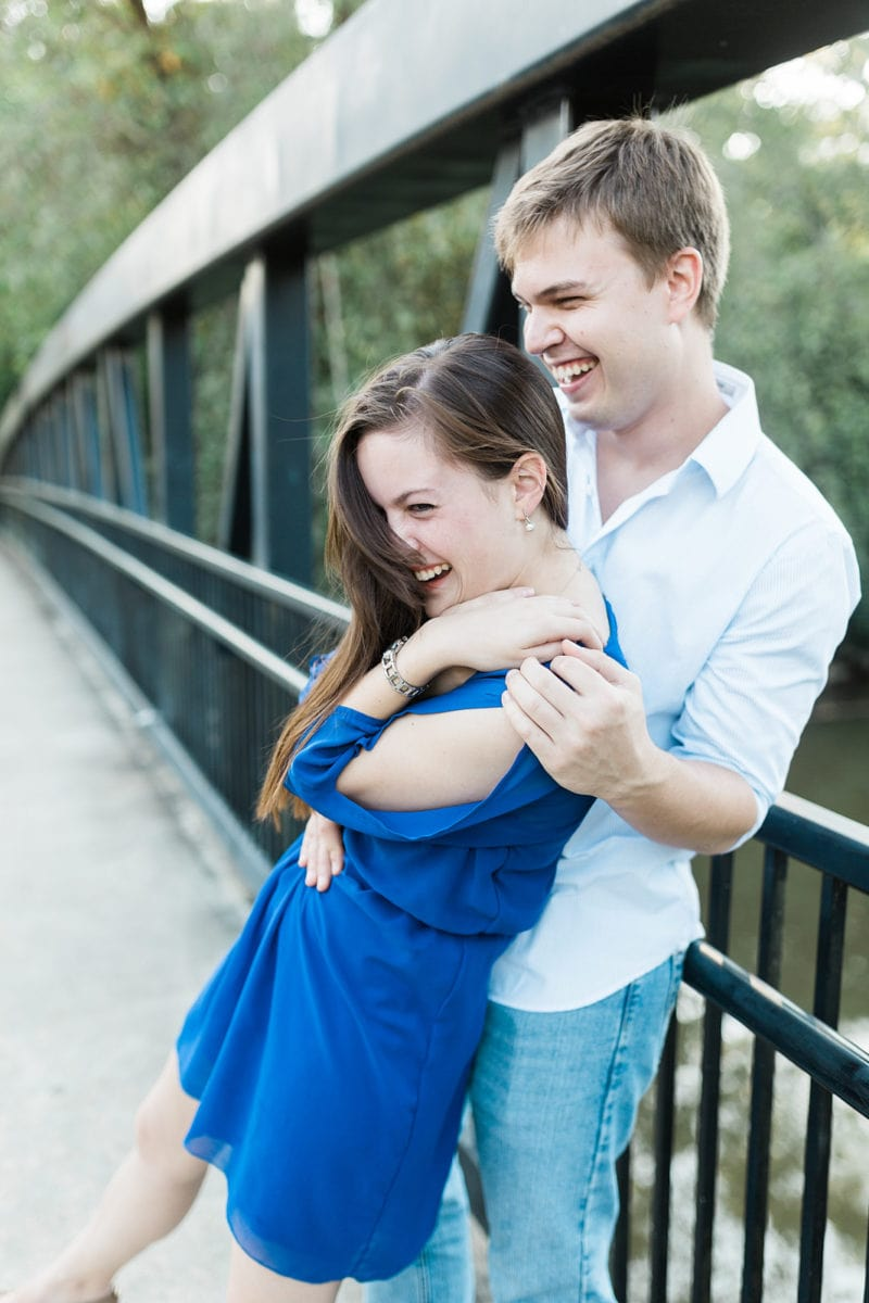 couple laughs on park bridge during engagement session in Roswell Atlanta