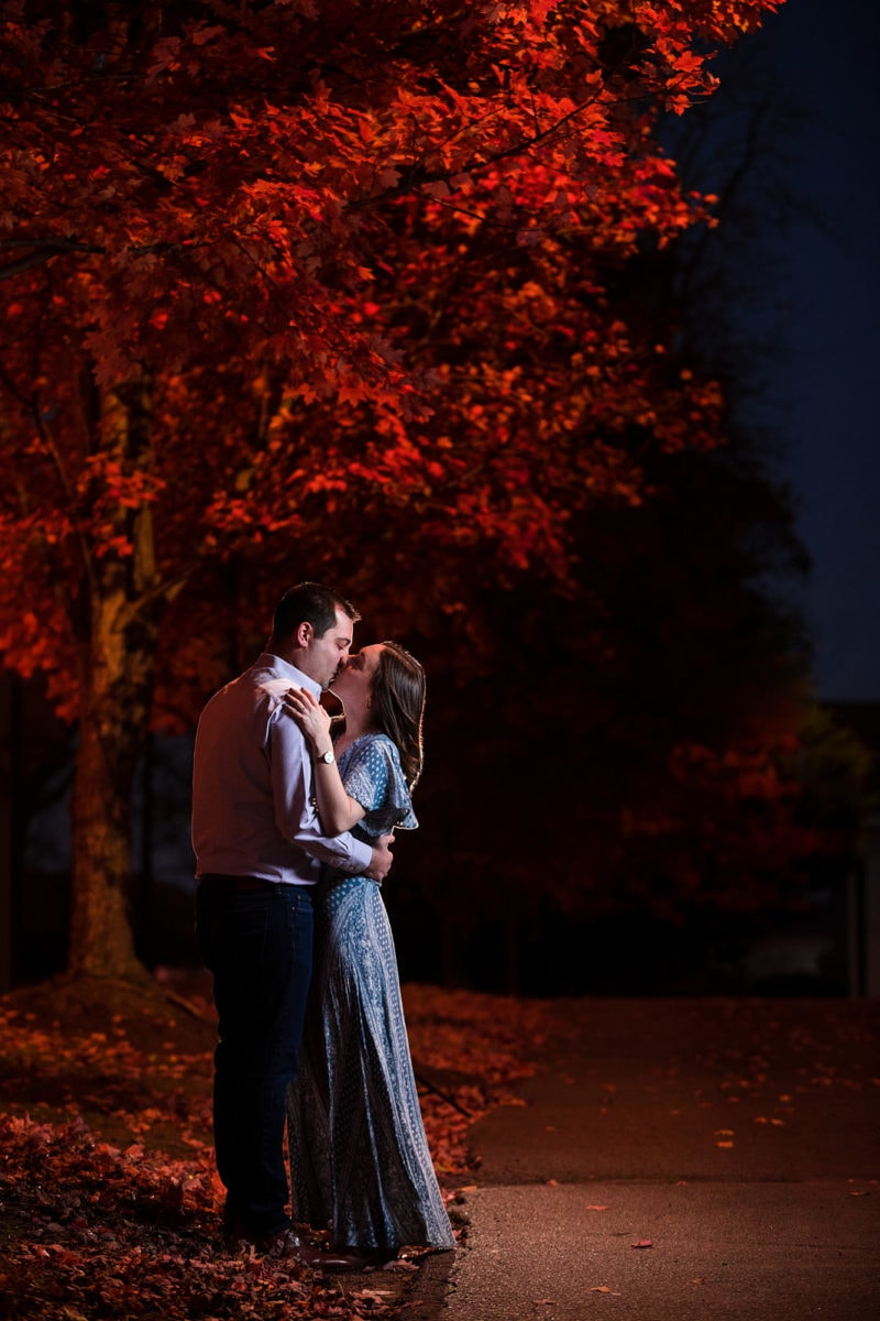 engaged couple kiss during fall night in downtown Roswell