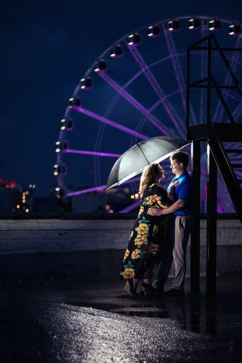 couple hugs in the rain with ferris wheel atlanta skyline