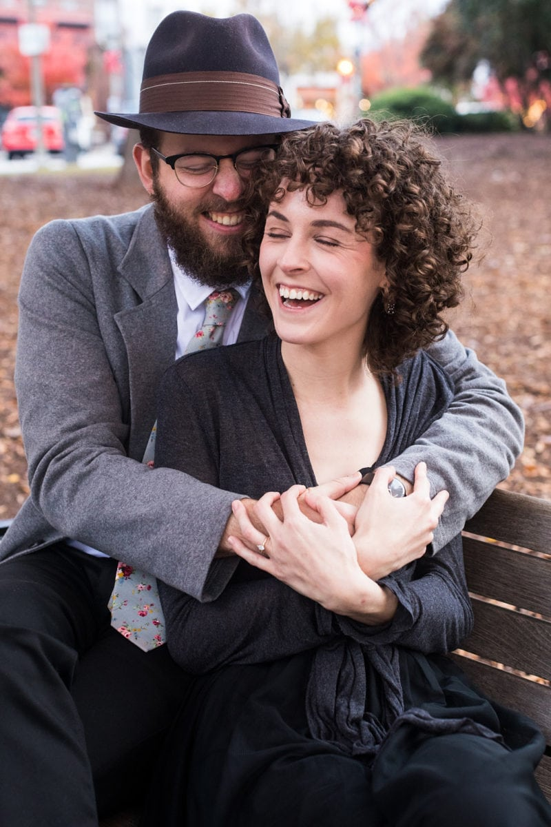Atlanta engaged couple laughs on park bench at Dekalb Historic Courthouse