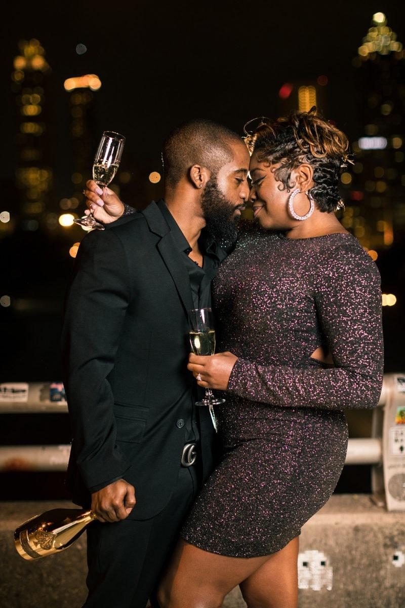 engaged couple shares glass of champagne over skyline at Jackson Street Bridge Atlanta