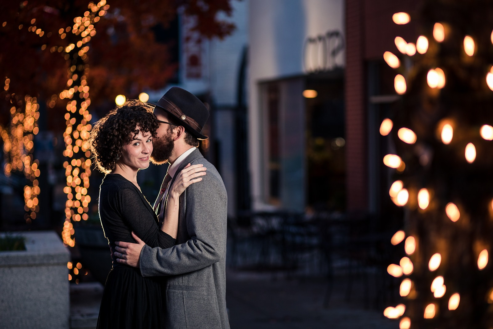 couple kisses for engagement with christmas lights at downtown Decatur Atlanta