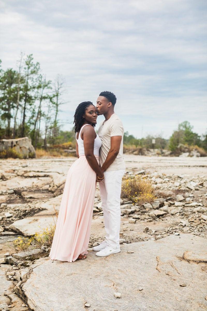 black couple kisses for engagement session at Arabia Mountain Atlanta