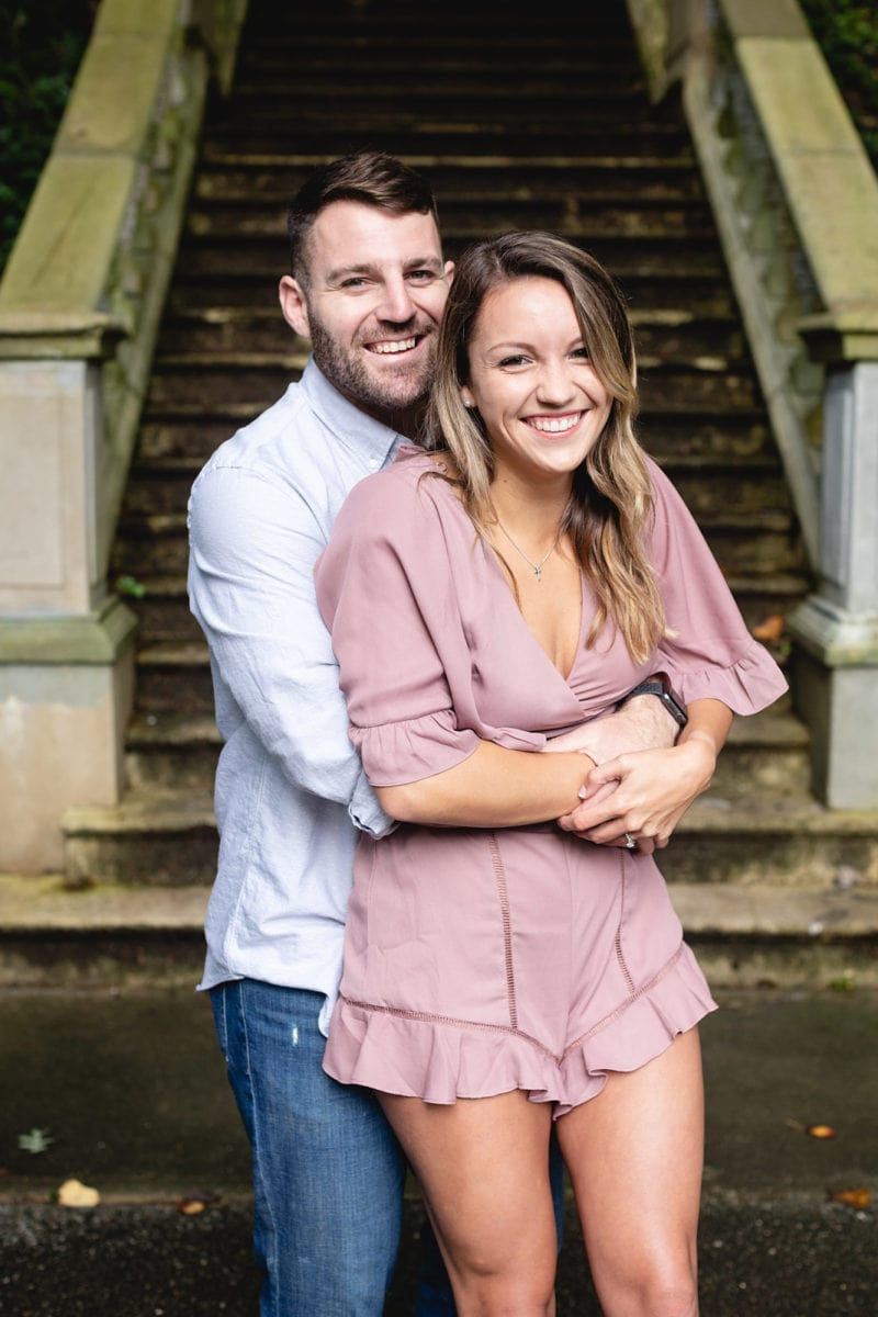 guy hugs fiance in front of steps for engagement at Cator Woolford Gardens by Mike Glatzer Photos