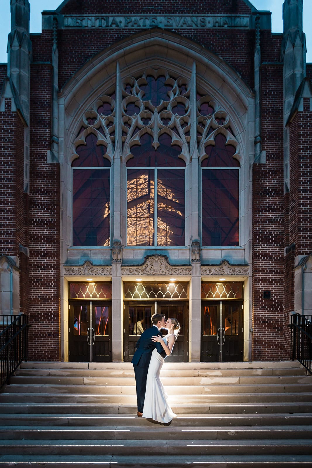 Groom dips and kisses bride on steps at Agnes Scott wedding
