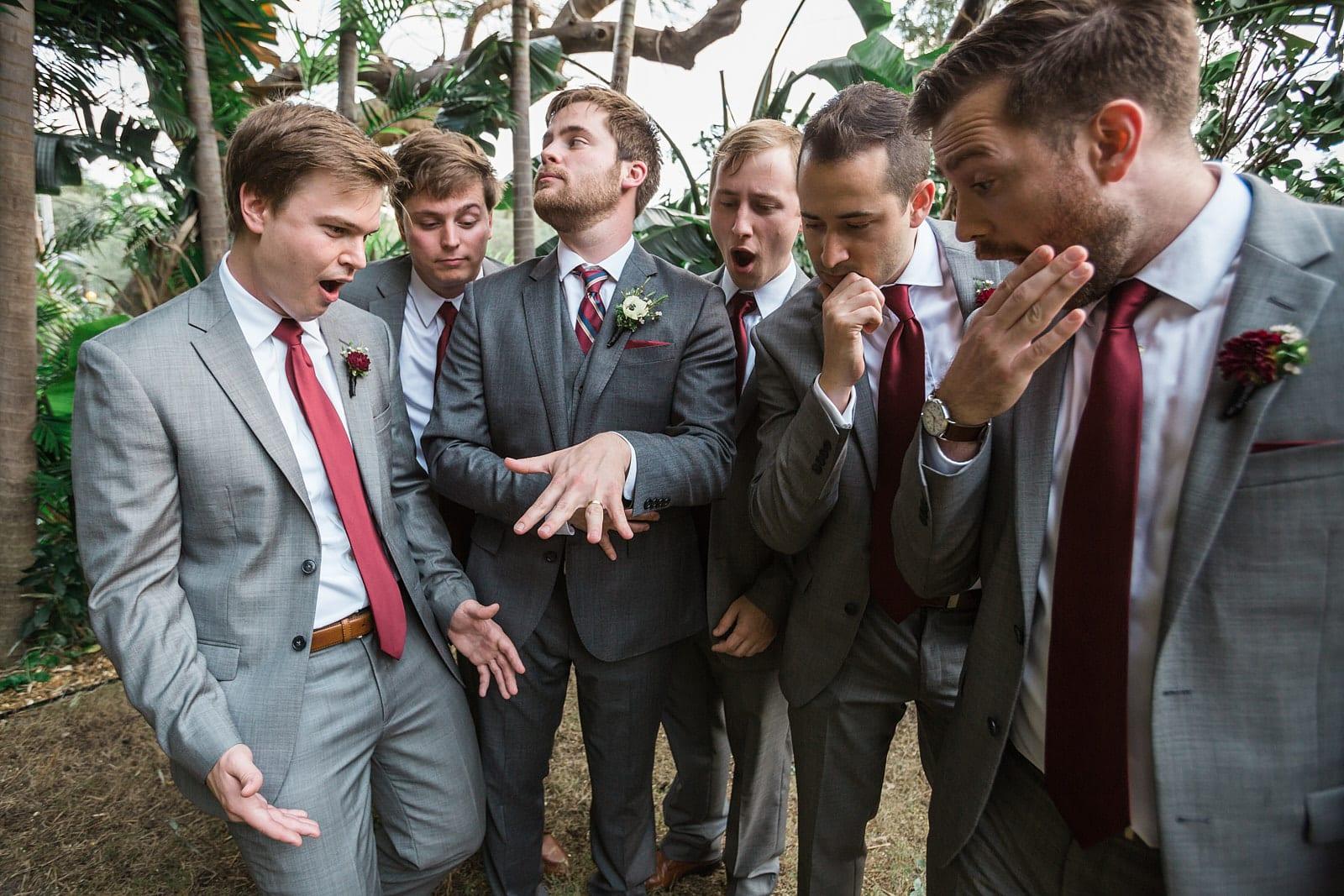 groom shows off wedding ring to groomsmen