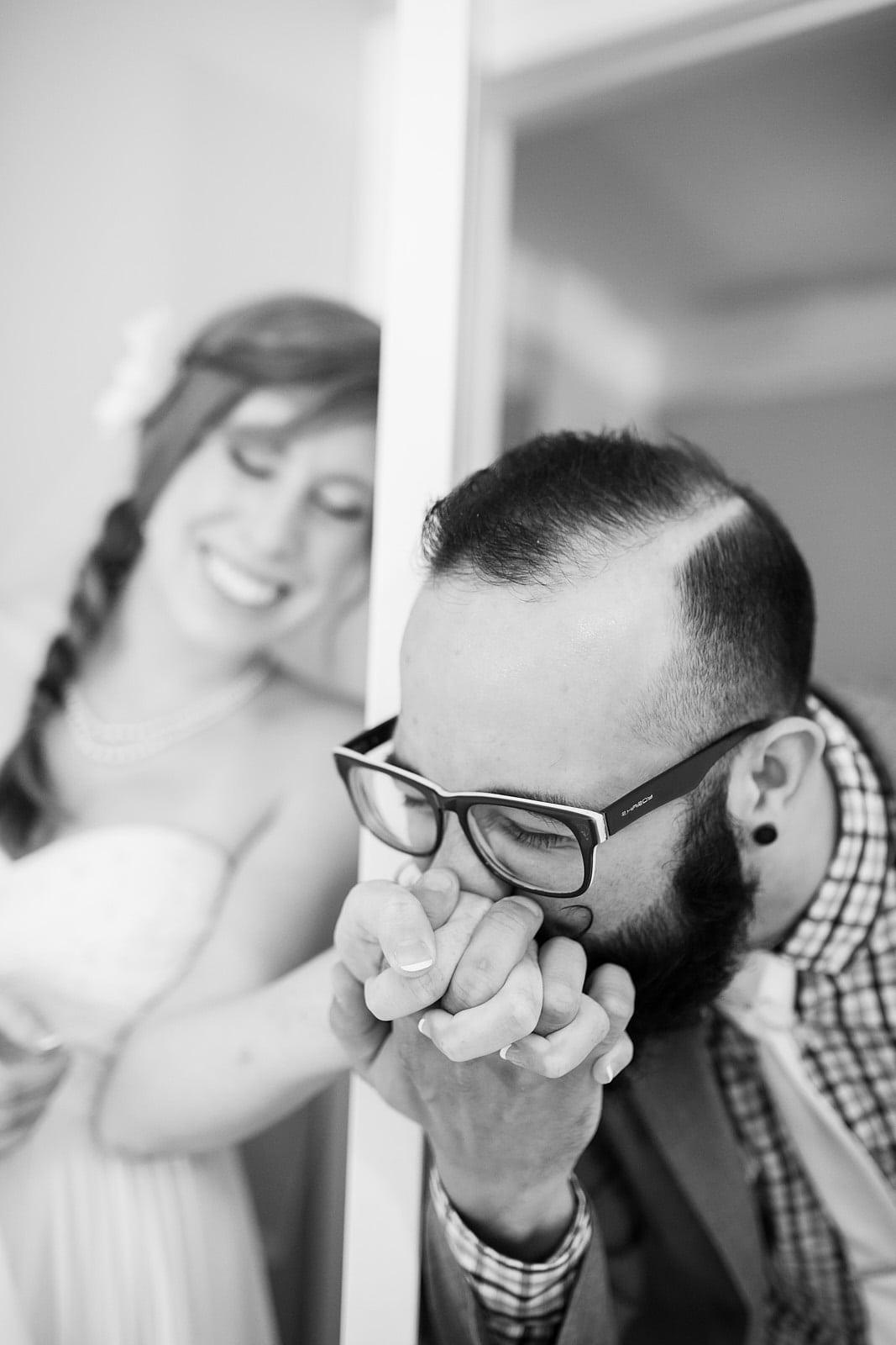Groom kissing bride's hand around door