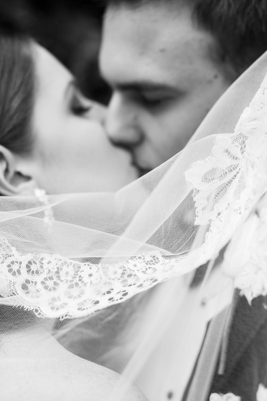 groom kisses bride behind wedding veil