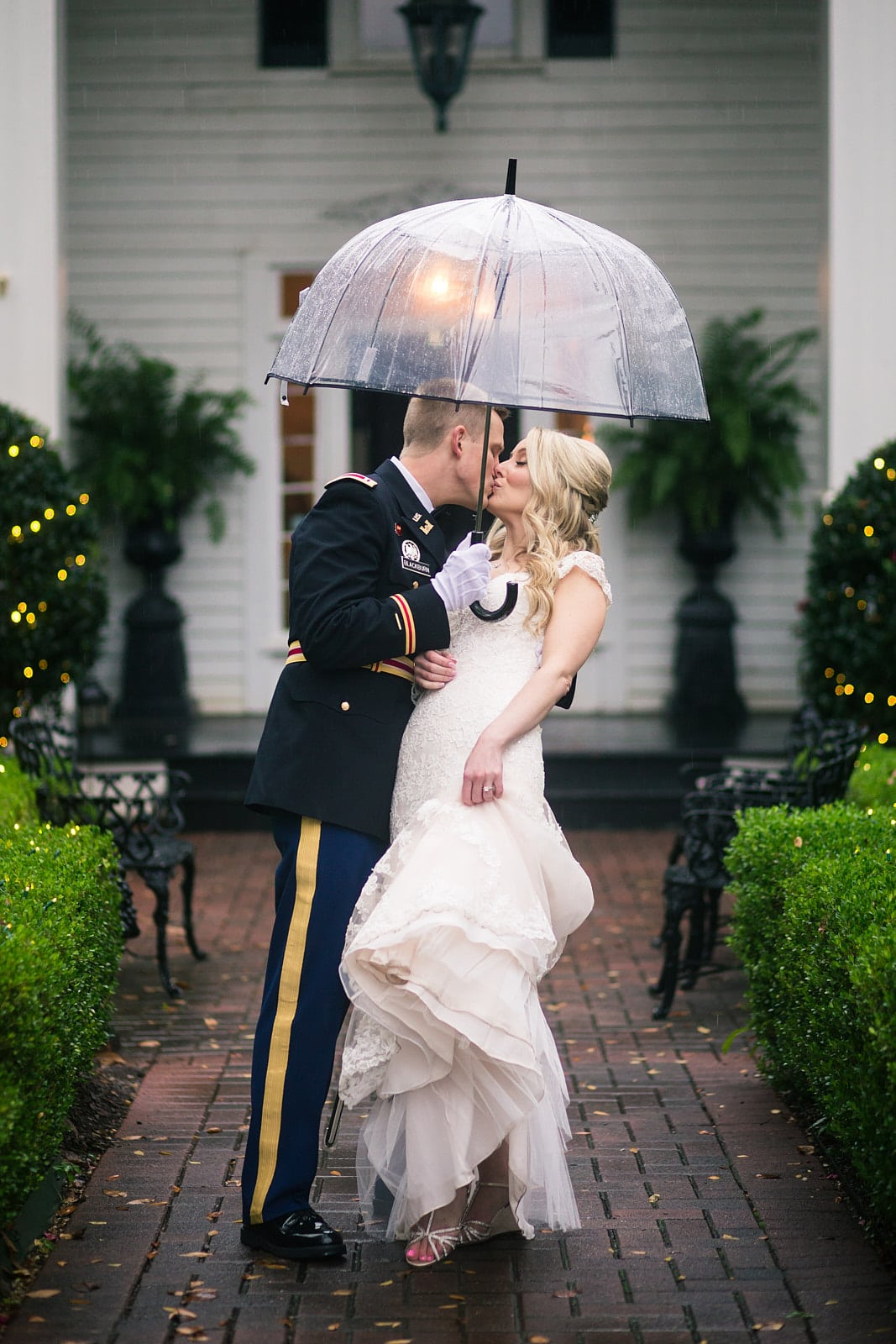 bride and groom under umbrella kiss in the rain at Roswell Founders Hall