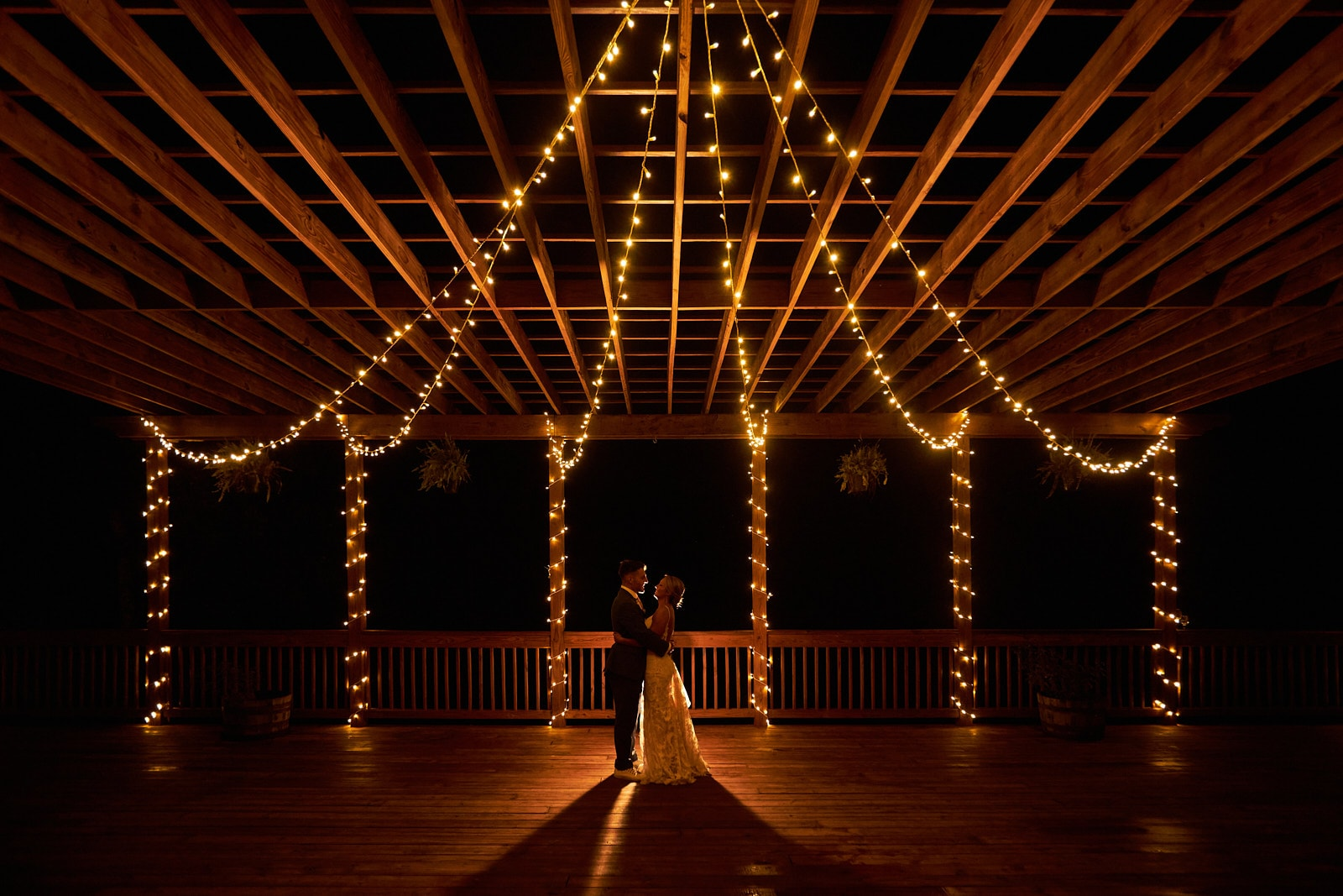 bride and groom kiss under string lights of willows farm