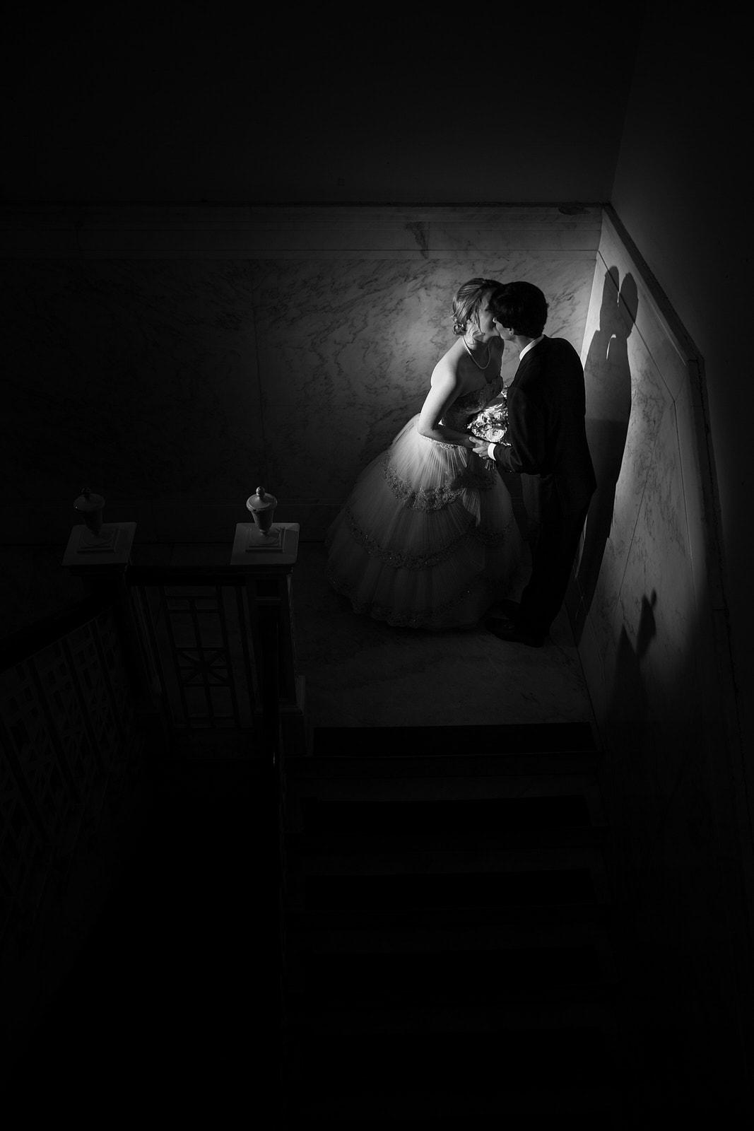 bride and groom kiss on stairs at Atlanta Historic Dekalb Courthouse wedding