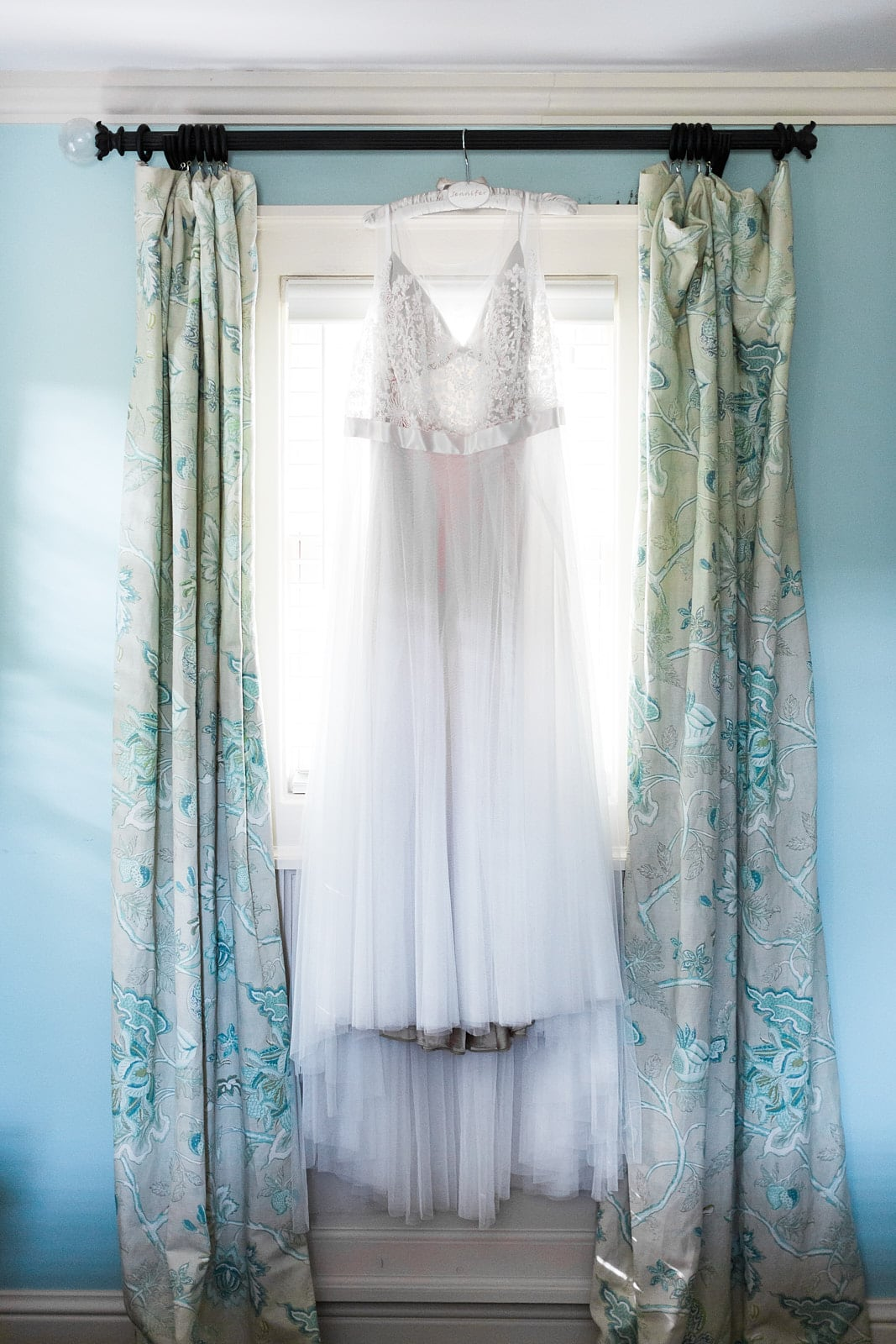 wedding dress hangs on window curtain Barnsley Gardens